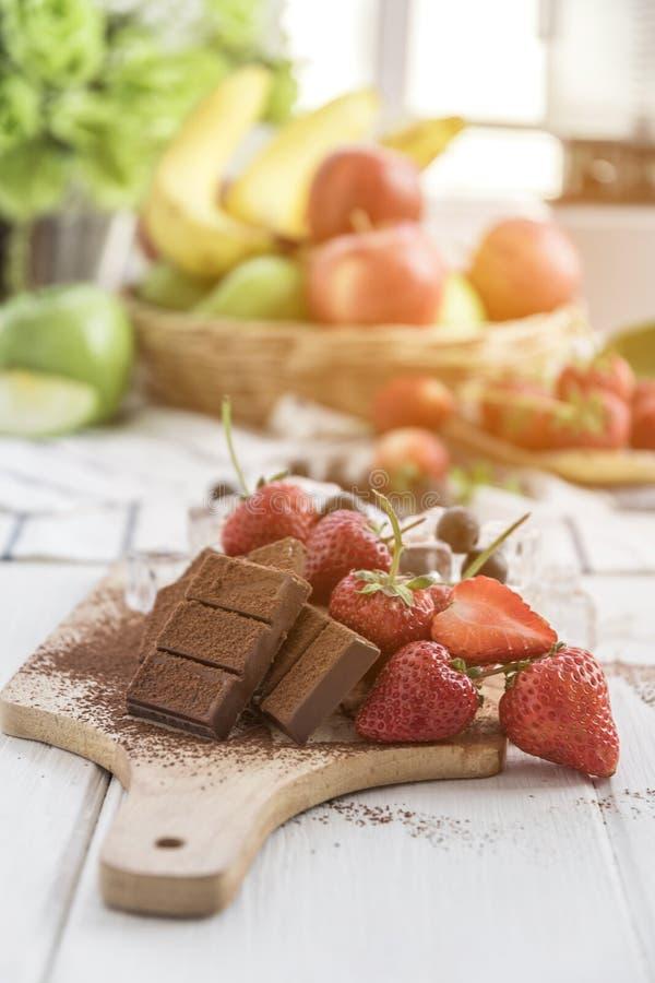 Chocolate com as bagas frescas na tabela de madeira fotos de stock royalty free