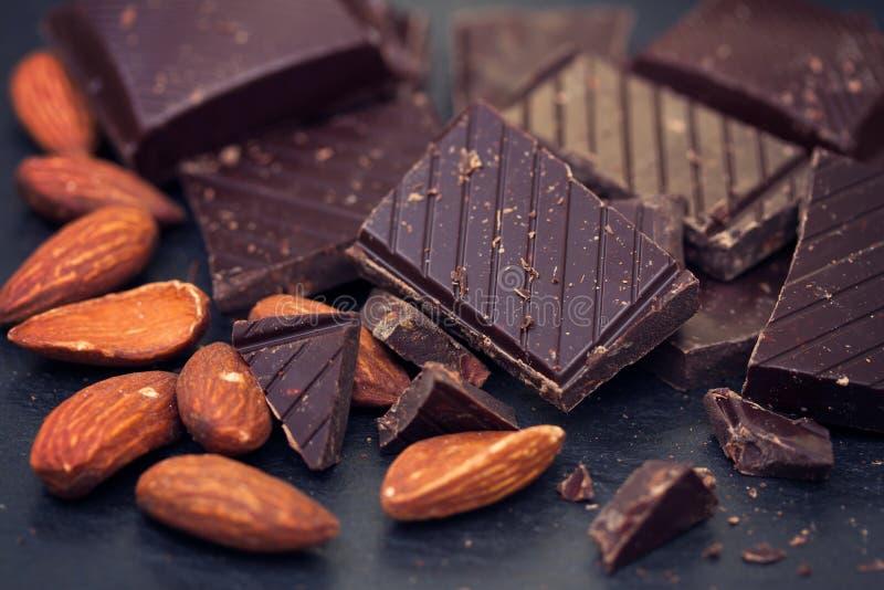 Chocolate con las almendras en fondo negro fotos de archivo