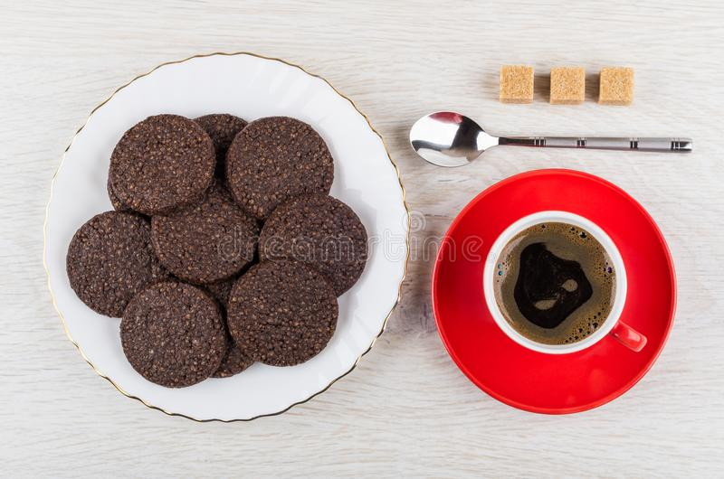 Chocolate cookies with airy rice, spoon, sugar, coffee in cup. Chocolate cookies with airy rice in plate, spoon, sugar cubes, coffee in red cup on saucer on stock photo