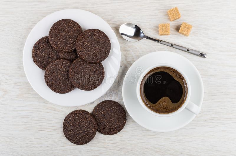 Chocolate cookies with airy rice, spoon, sugar cubes, coffee. Chocolate cookies with airy rice in white plate, spoon, sugar cubes, coffee in cup on saucer on stock photo
