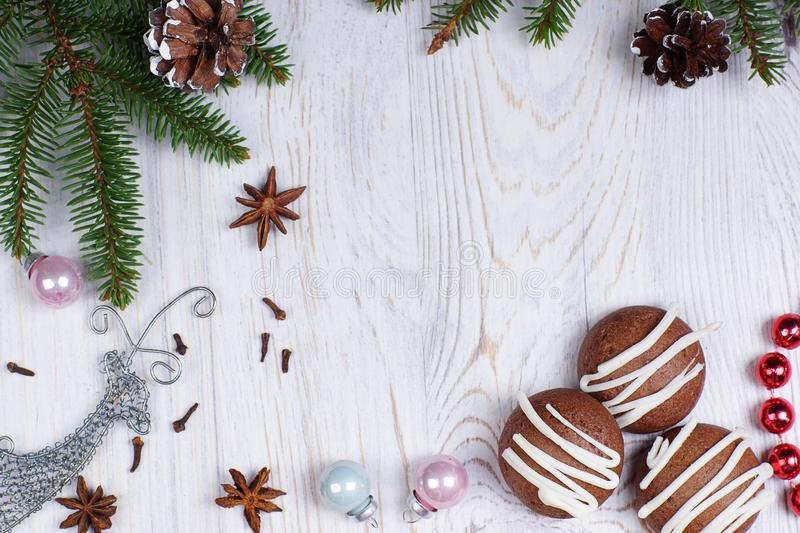 Chocolate cookies, Christmas tree branches and decorations on a light wooden background. royalty free stock photos