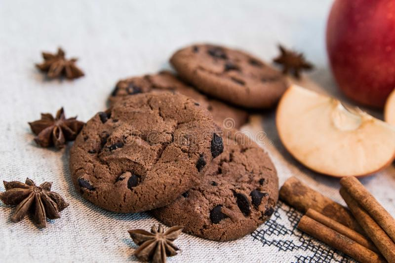 Chocolate cookies with cinnamon, apple and anise. On embroided table cloth stock photo