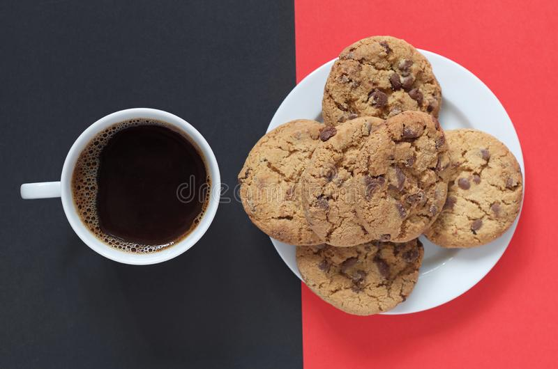 Chocolate cookies and coffee. Chocolate cookies and cup of coffee on a red-black background, top view stock photos