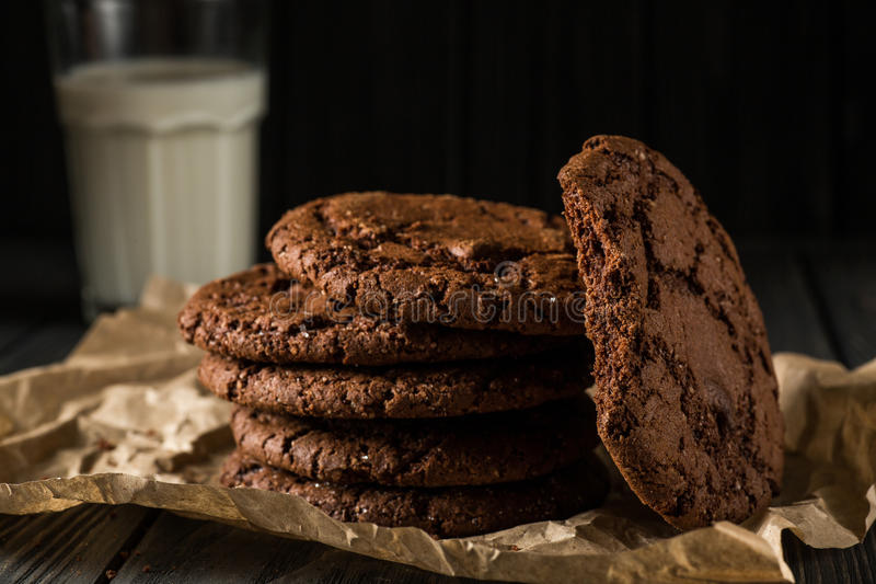 Chocolate cookies on craft paper with glass of milk. Stack of Chocolate chip cookies on paper on wooden background royalty free stock photo