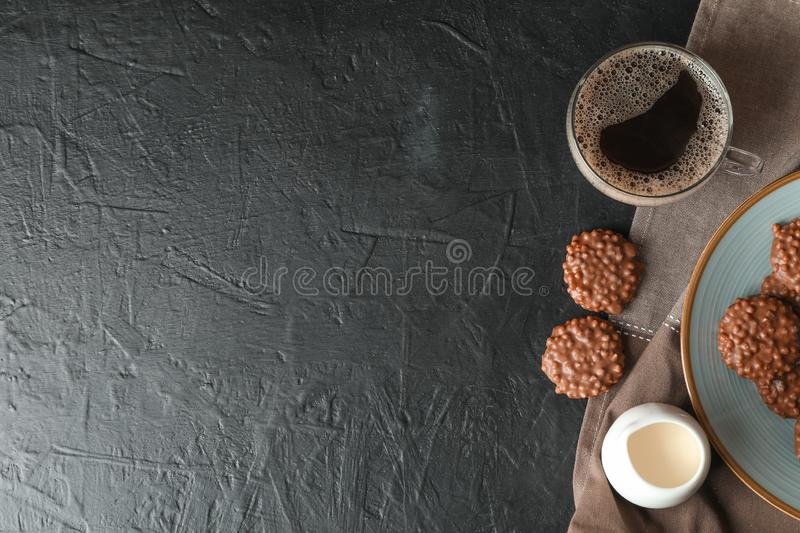 Chocolate cookies, cup of coffee and milk on black table. Space for text stock photography