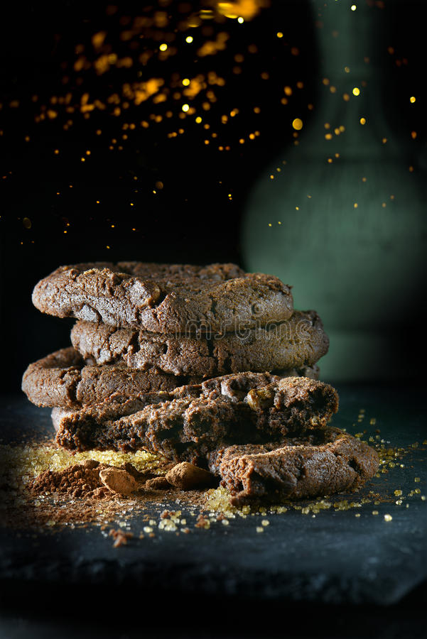 Chocolate Cookies II. Christmas themed triple chocolate chip cookies stacked with scattered sugar and cocoa on a slate base. Shot against a dark, rustic stock image
