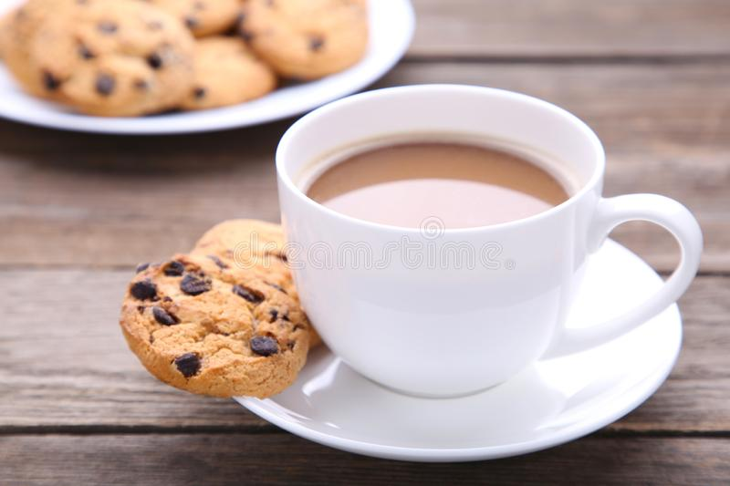 Chocolate cookies on plate and cup of coffee on grey background stock photos