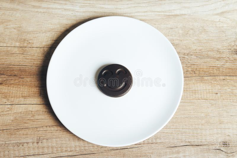 Chocolate cookies with a smiling face, smile, lie on a white plate standing on a wooden table. place for the inscription stock photos