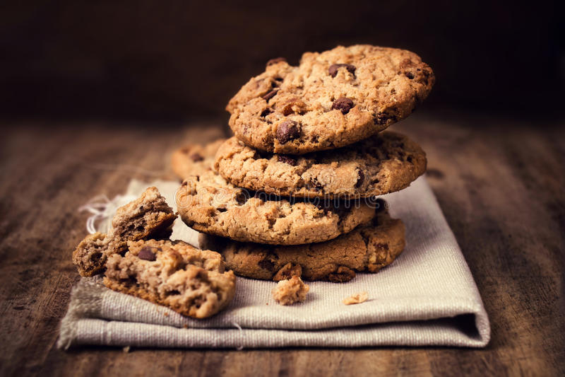 Chocolate cookies on white linen napkin on wooden table. Chocolate chip cookies shot on coffee colored cloth, closeup. royalty free stock photos