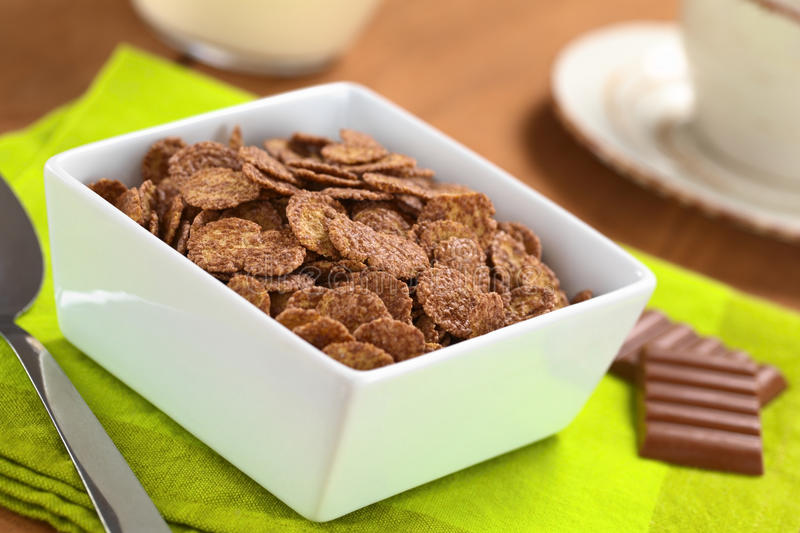 Chocolate Corn Flakes. Bowl of chocolate corn flakes cereal with spoon and chocolate bars, a cup and milk in the back (Selective Focus, Focus in the middle of stock images