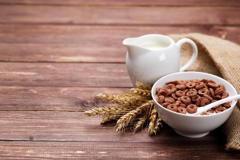 Chocolate corn flakes in bowl with milk. And wheat ears on wooden table royalty free stock photography