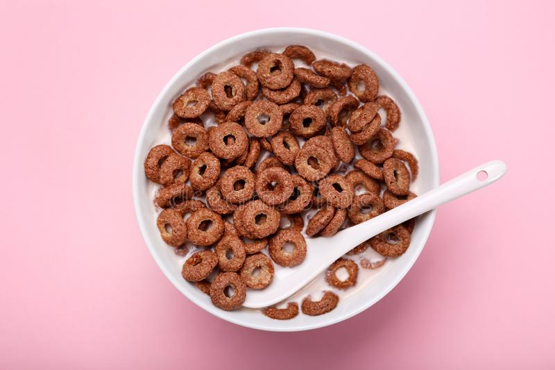 Chocolate corn flakes. In bowl with milk and spoon on pink background stock photo