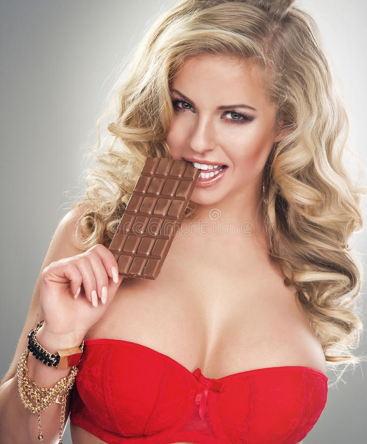 chocolate cortante da jovem mulher loura imagem de stock royalty free
