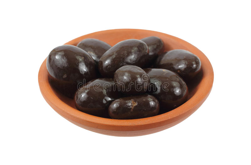 Chocolate Covered Almonds in Terra Cotta Dish. A small serving of chocolate covered almonds stock photos
