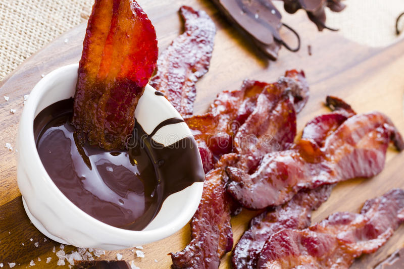 Chocolate covered bacon. With salt stock images