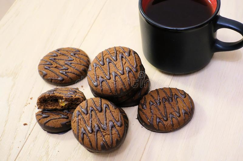 Chocolate covered cookies on a wooden table with a cup of coffee. Breakfast. Dessert royalty free stock image
