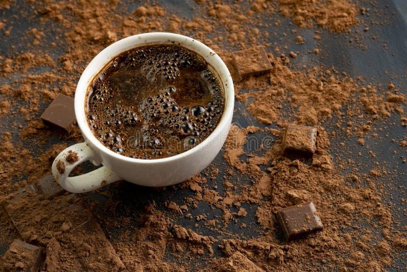 chocolate cozinhando quente fresco em um copo, em uma barra de chocolate e em um cacau nas tabelas escuras fotos de stock royalty free