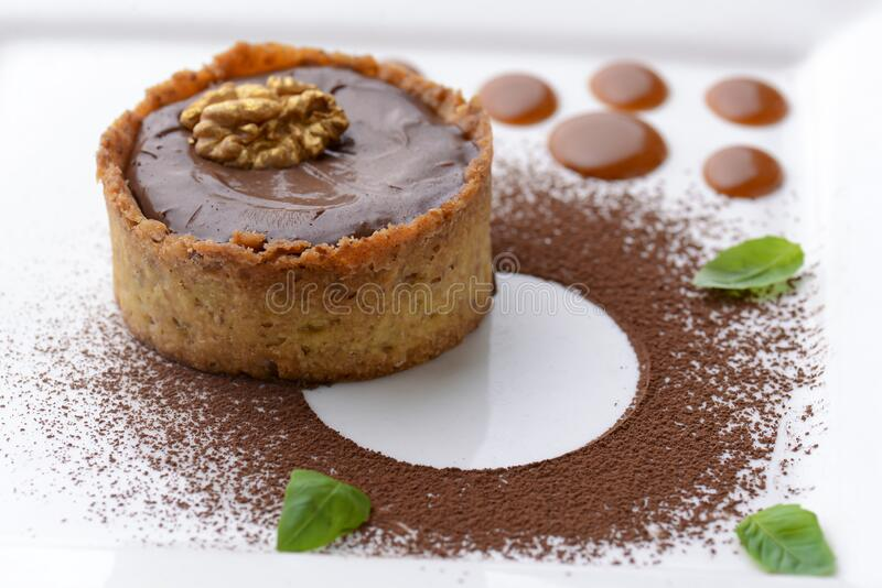 Chocolate creme brulee with cocoa powder, walnuts and mint leaf. Traditional French vanilla cream dessert. Chocolate creme brulee with cocoa powder, walnuts and stock photo