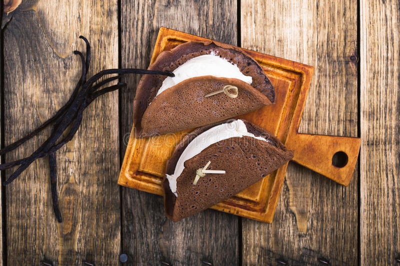 Chocolate crepes with cream. Homemade chocolate crepes with vanilla cream on wooden board, top view stock image