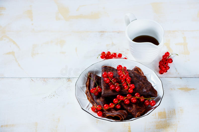 Chocolate crepes with currants. Delicious chocolate crepes with fresh red currants and maple syrop on plate. Light white wooden background. Selective focus. Copy royalty free stock photo