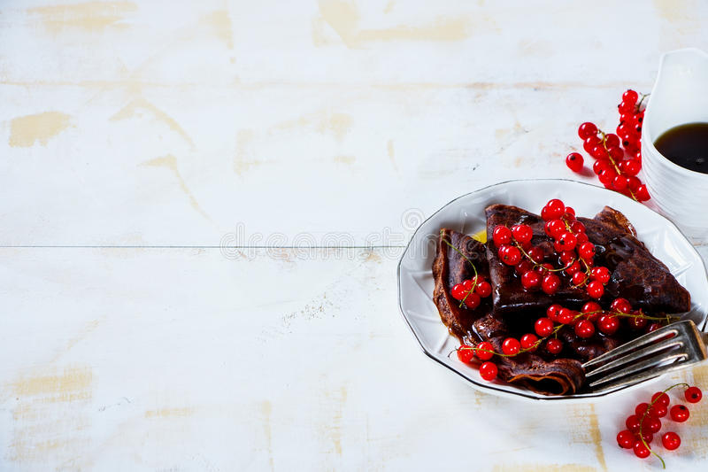 Chocolate crepes with currants. Homemade chocolate crepes with fresh red currants and maple syrop on plate. Light white wooden background. Selective focus. Copy royalty free stock image