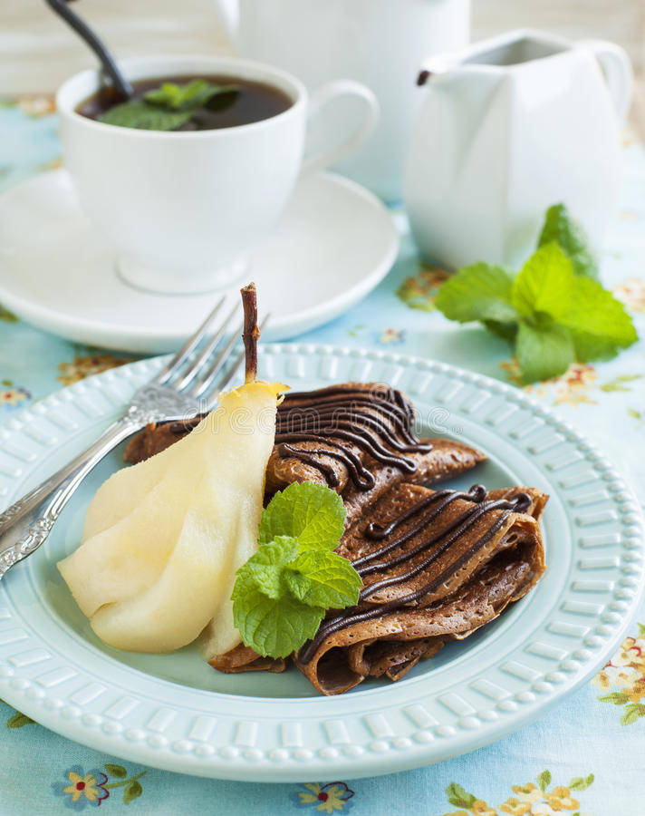 Chocolate crepes with poached pear in syrup. And cup of tea stock photography