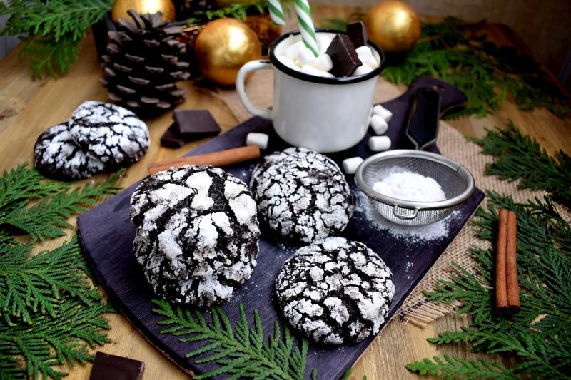 Chocolate crinkle cookies covered with sugar powder. On a wooden board stock photography