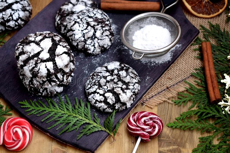 Chocolate crinkle cookies covered with sugar powder. On a wooden board stock image