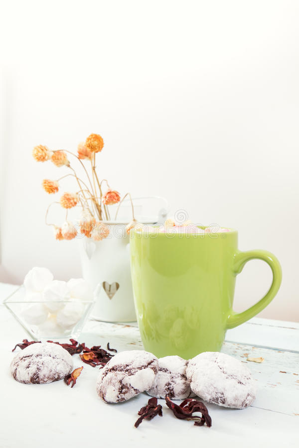 Chocolate crinkles cookies and hot chocolate. Chocolate crinkles cookies, marshmallows, hot chocolate with colorful marshmallows and dried flowers on a light royalty free stock images