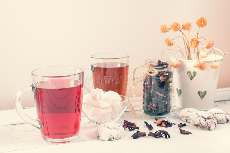 Chocolate crinkles cookies, marshmallows, tea. Chocolate crinkles cookies, marshmallows, Hibiscus tea, dried flowers on a light wooden table against white stock photo