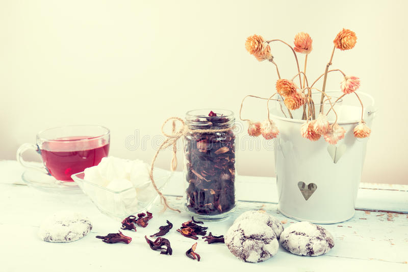 Chocolate crinkles cookies, marshmallows, tea. Chocolate crinkles cookies, marshmallows, Hibiscus tea, dried flowers on a light wooden table against white stock image