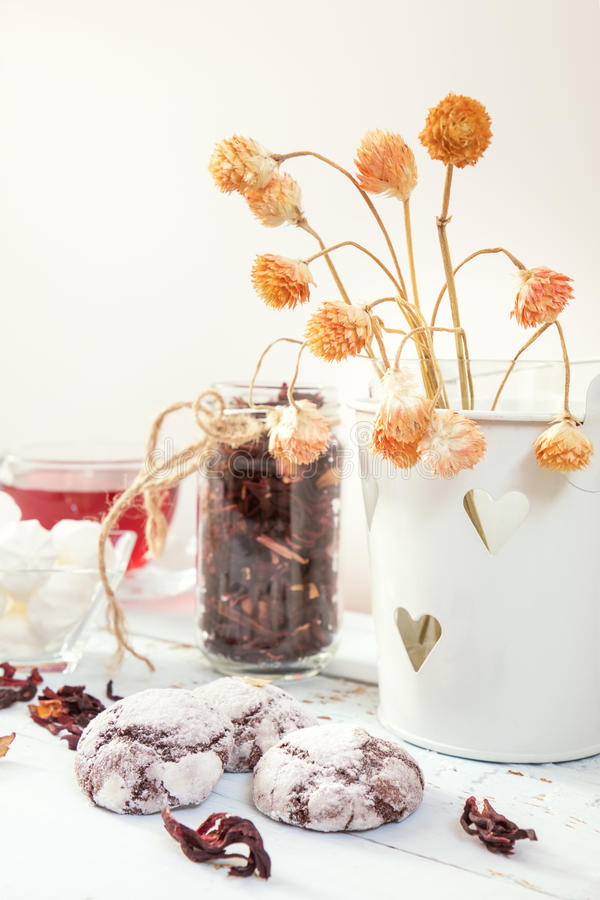 Chocolate crinkles cookies, marshmallows, tea. Chocolate crinkles cookies, marshmallows, Hibiscus tea, dried flowers on a light wooden table against white royalty free stock photography