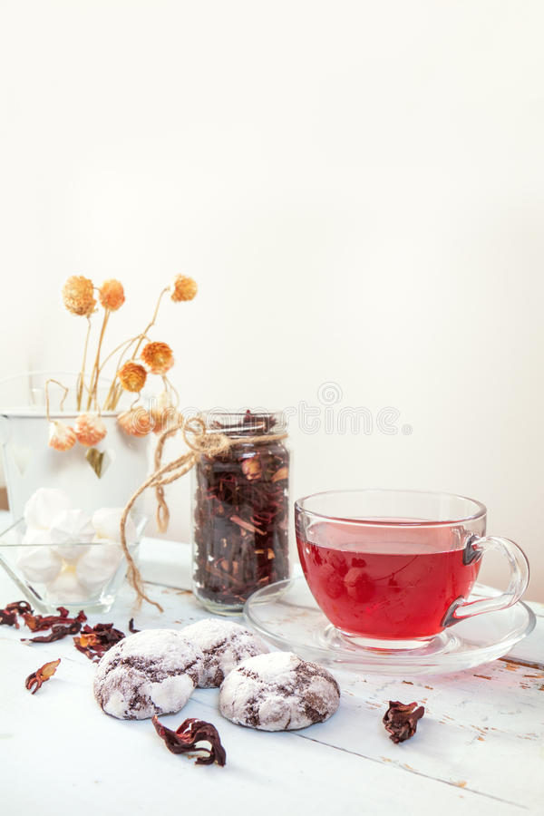 Chocolate crinkles cookies, marshmallows, tea. Chocolate crinkles cookies, marshmallows, Hibiscus tea, dried flowers on a light wooden table against white royalty free stock images