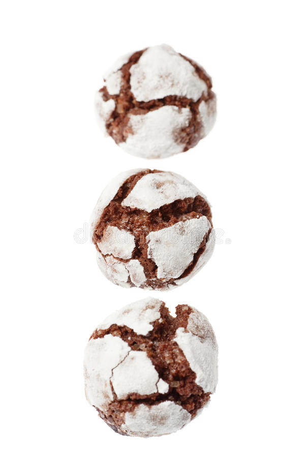 Chocolate crinkles in a row. Three chocolate crinkles in a row, isolated on white. Focus is on the middle cookie royalty free stock photos