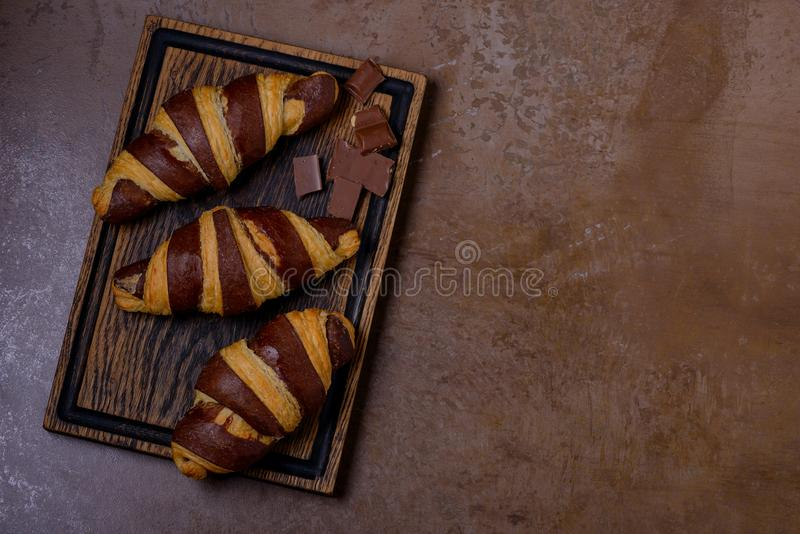Chocolate croissant and chocolatier on table. French pastry royalty free stock image