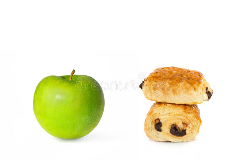 Chocolate croissants and a green apple on white background, healthy or unhealthy food choice stock photo