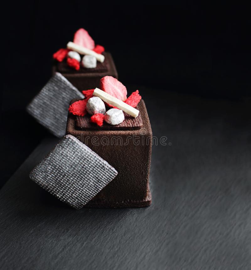 Chocolate cube desserts with dried strawberry and meringue. On black background royalty free stock image