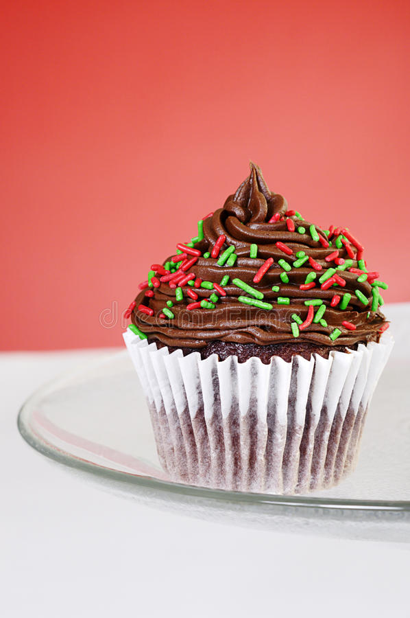 Chocolate cupcake. Christmas themed cupcake decorated with red and green sprinkles on red background royalty free stock image