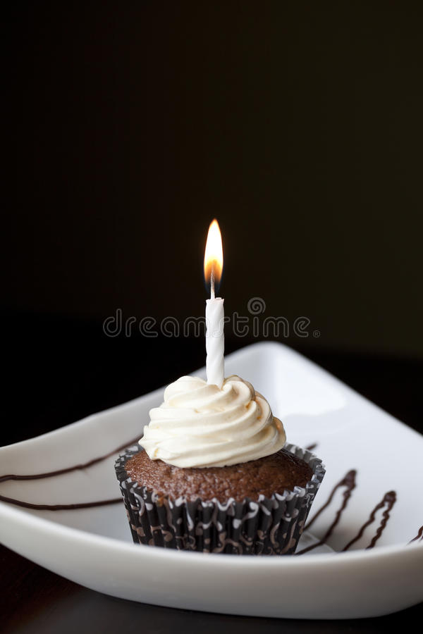 Chocolate Cupcake with a Burning Birthday Candle royalty free stock images