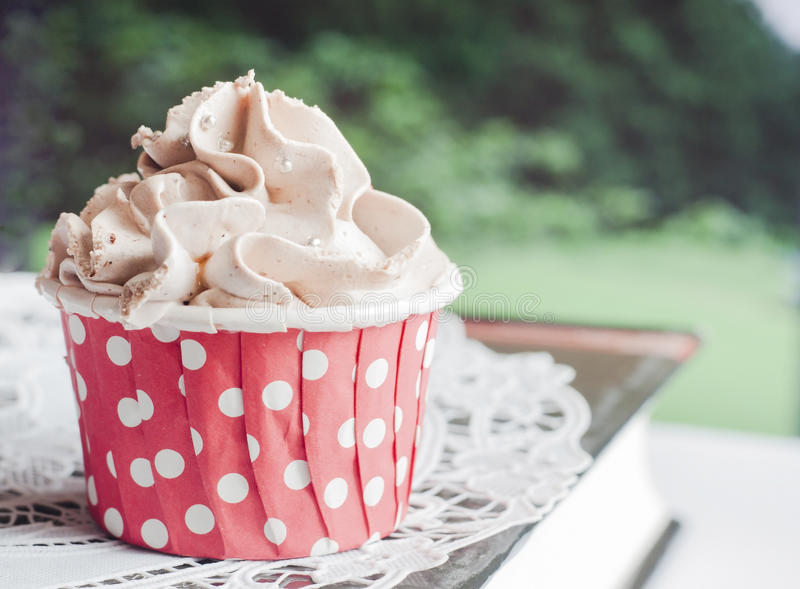 Chocolate cupcake. With red cup and brown cream royalty free stock photo