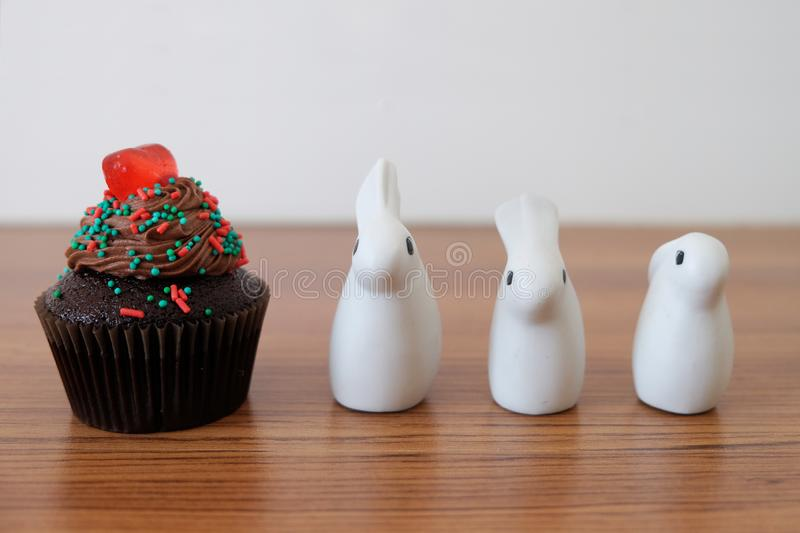 Chocolate cupcake with red heart jelly and three small ceramic rabbits royalty free stock photos