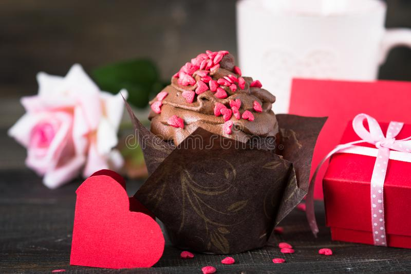 Chocolate cupcake with whipped cream for Valentine`s Day. Chocolate cupcake with whipped cream, sprinkled with red hearts. Sweet Food baking for Valentine`s Day royalty free stock images