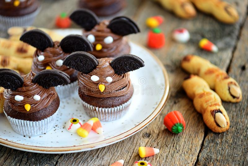 Chocolate cupcakes `bats` and shortbread cookies `witch`s fingers` - delicious bakery sweets for the celebration of Halloween. royalty free stock photos