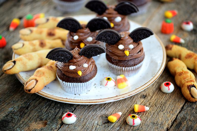 Chocolate cupcakes `bats` and shortbread cookies `witch`s fingers` - delicious bakery sweets for the celebration of Halloween. stock image