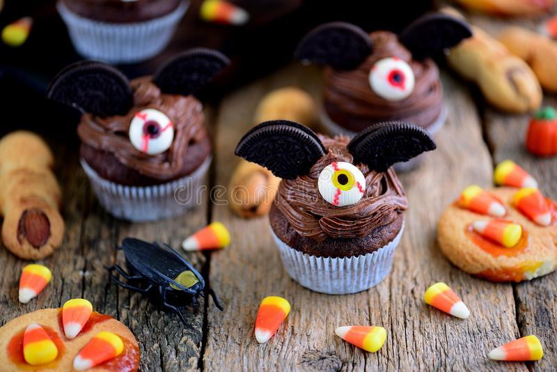 Chocolate cupcakes `bats` and shortbread cookies `witch`s fingers` - delicious bakery sweets for the celebration of Halloween. royalty free stock image