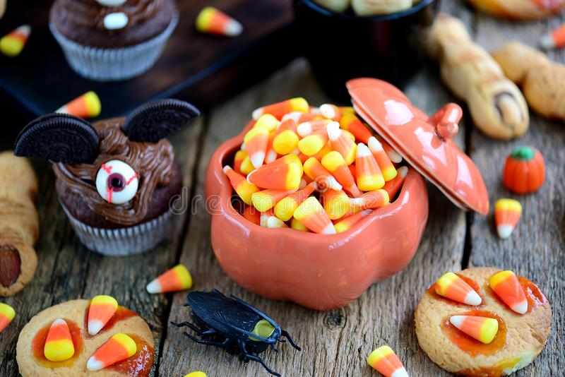 Chocolate cupcakes `bats` and shortbread cookies `witch`s fingers` - delicious bakery sweets for the celebration of Halloween. stock photo