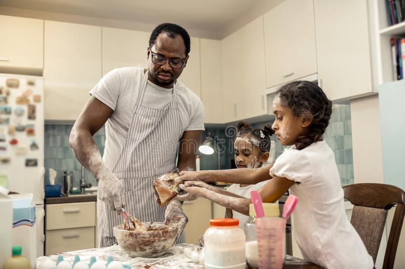 Father feeling happy cooking chocolate cupcakes with daughters. Chocolate cupcakes. Father wearing apron feeling happy cooking chocolate cupcakes with daughters royalty free stock images