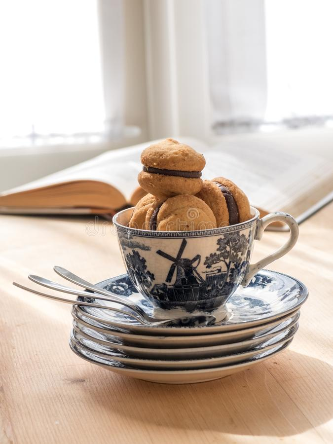Chocolate cupcakes in teacup, book on background. royalty free stock photography