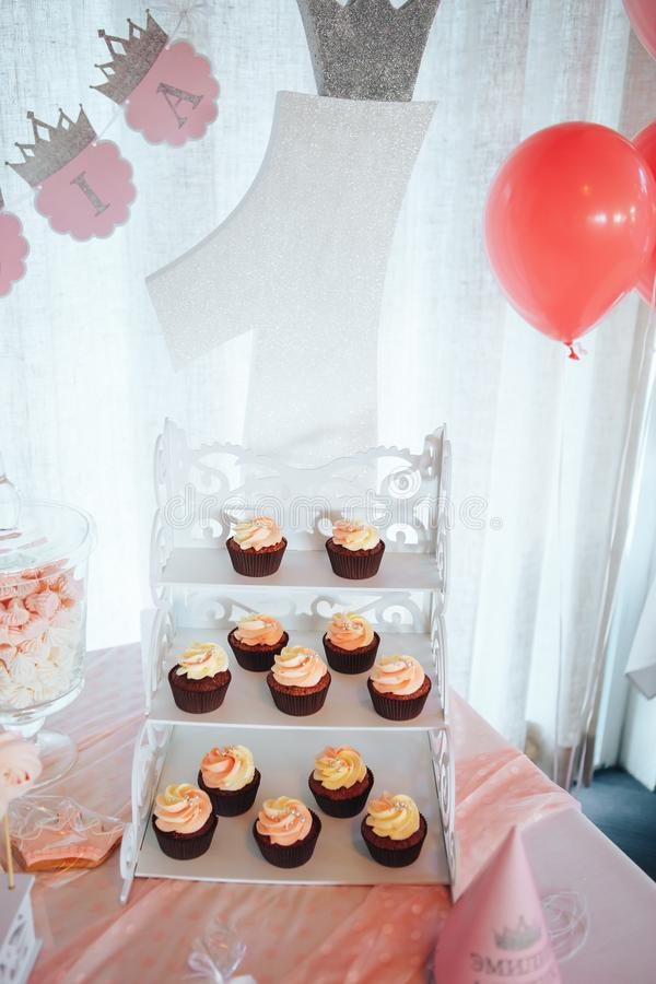 Chocolate cupcakes on a white wooden stand. Sweet table and big cake for first birthday stock photography