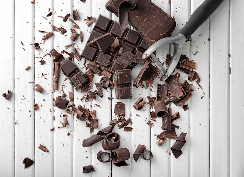 Chocolate curls and peeler on table royalty free stock image